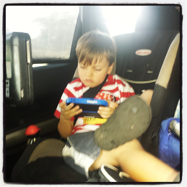 Chilling out, playing his Nintendo 2DS on a very long car trip earlier this year.